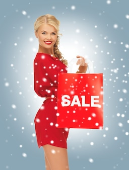 Bild der schönen frau im roten kleid mit einkaufstasche
