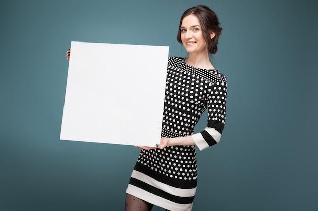 Bild der schönen frau in der gesprenkelten kleidung, die mit großem leerem plakat in den händen steht
