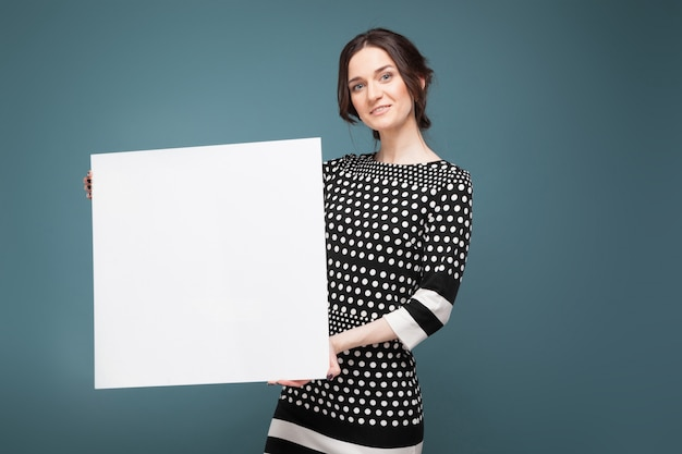 Bild der schönen frau in der gesprenkelten kleidung, die mit großem papier in den händen steht