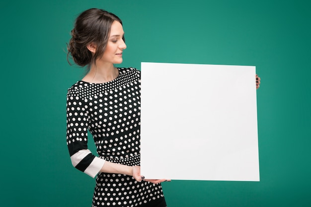 Bild der schönen frau in der gesprenkelten kleidung, die mit papier in den händen steht