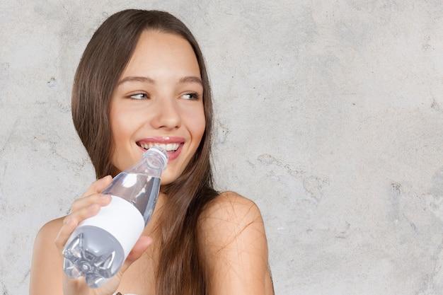 Bild der schönen frau mit flasche wasser
