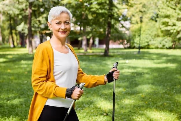 Bild der schönen freudigen älteren reifen frau in der gelben strickjacke, die stöcke für nordic walk hält, aktiven gesunden lebensstil genießt, voller energie fühlt, mit glücklichem lächeln