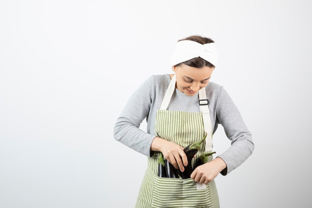 Bild der schönen glücklichen hausfrau legt auberginen in die schürze