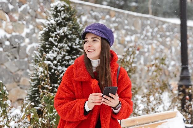 Bild der schönen jungen frau draußen im schneewinterparkwald unter verwendung des mobiltelefons.