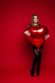 Bild der schönen kaukasischen frau im schwarzen kleid hält herzballons in ihren händen auf rot