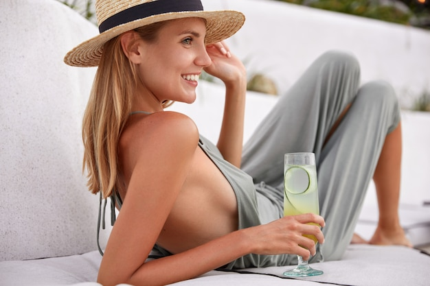 Bild der schönen lächelnden frau mit gesunder reiner haut und positivem lächeln, trägt strohhut und sommerkostüm, trinkt frischen cocktail, schaut glücklich in die ferne. hübsche frau mit kaltem getränk