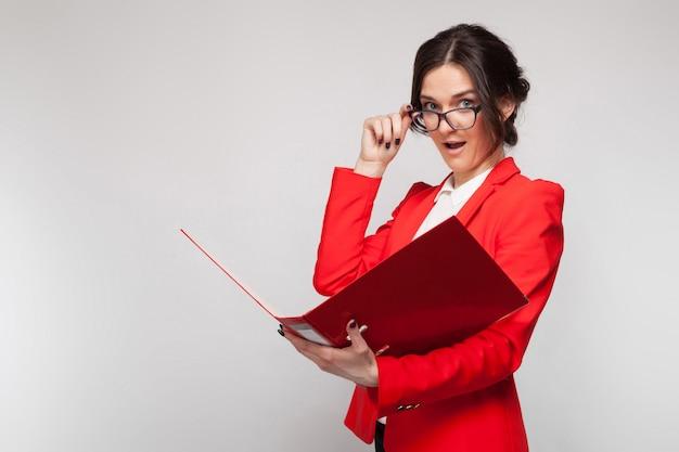 Bild der schönheit im roten blazer, der mit dokumenten in den händen steht