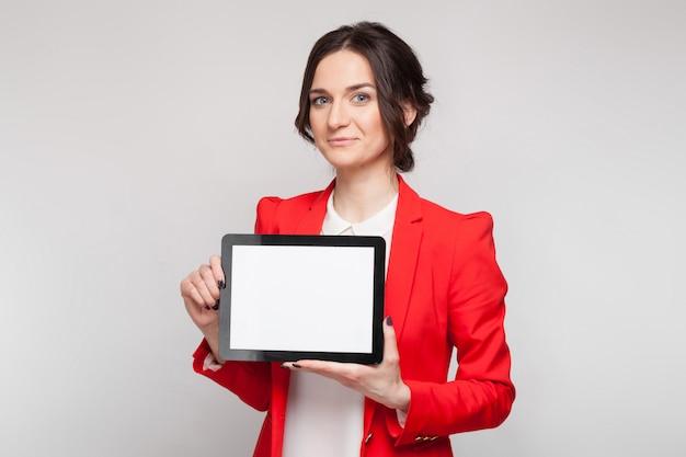 Bild der schönheit im roten blazer, der mit tablette in den händen steht