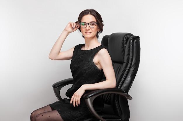 Bild der schönheit im schwarzen kleid, das auf einem lehnsessel sitzt