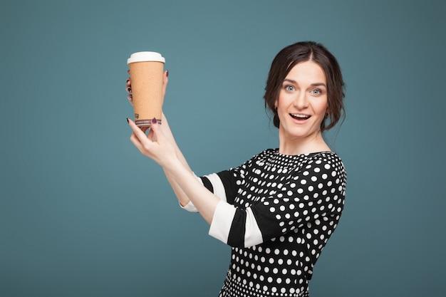 Bild der schönheit in der gesprenkelten kleidung, die mit coffe in den händen steht