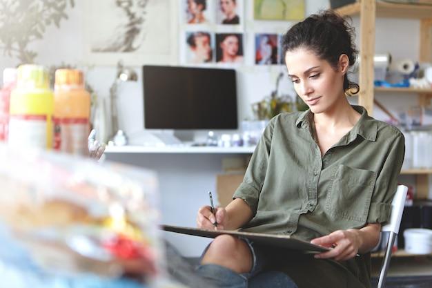 Bild der talentierten professionellen jungen designerin im hemd der khakifarbenen farbe, die in ihrer werkstatt sitzt, skizziert, am design der neuen schmuckkollektion arbeitet, konzentriert und konzentriert schaut