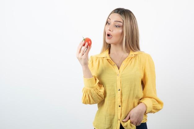 Bild der überraschten frau, die rote tomate auf weiß betrachtet.