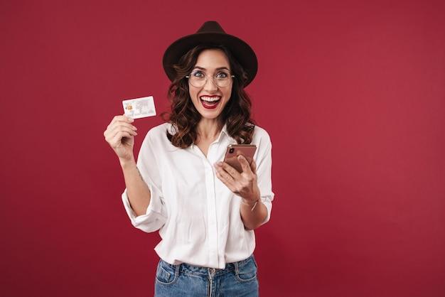 Bild der überraschten optimistischen jungen frau in den gläsern lokalisiert auf der roten wand unter verwendung des handys, das kreditkarte hält.