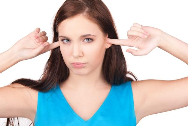 Bild der unglücklichen teenagerin mit den fingern in den ohren
