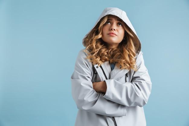 Bild der unzufriedenen frau 20s, die regenmantel mit kapuze trägt, die nach oben schaut