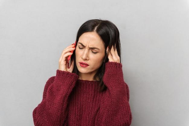 Bild der unzufriedenen jungen frau gekleidet im burgunderfarbenen pullover, der durch handy lokalisiert spricht.