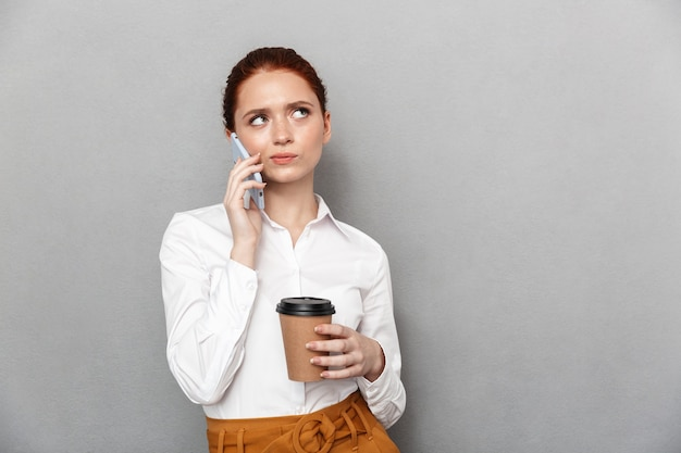 Bild der verwirrten jungen hübschen rothaarigen geschäftsfrau, die lokalisiert über grauer wand aufwirft, die durch trinkenden kaffee des handys spricht.
