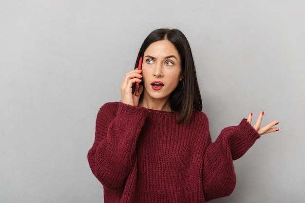 Bild der verwirrten unzufriedenen jungen frau gekleidet im burgunderfarbenen pullover, der durch handy lokalisiert spricht.