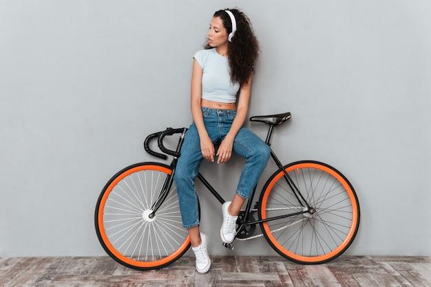 Bild der vollen länge der geschlagenen lockigen frau, die mit fahrrad steht und musik durch den kopfhörer über grauem hintergrund hört