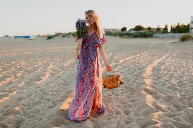 Bild der vollen länge der hübschen blonden frau mit lavendelstrauß, der auf dem strand geht. sonnenuntergangsfarben.