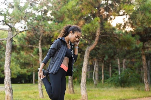 Bild der weiblichen afroamerikanerfrau 20s, die schwarzen trainingsanzug trägt, der sport treibt und ihren körper im grünen park streckt