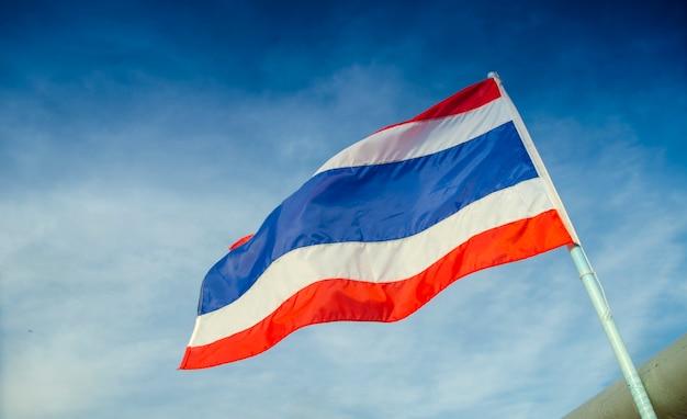 Bild der wellenartig bewegenden thailändischen flagge von thailand mit hintergrund des blauen himmels.
