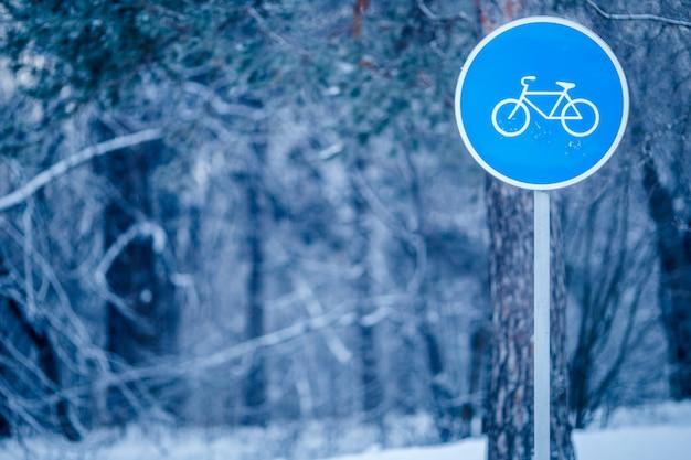 Bild der winterlandschaft mit verkehrsschild des fahrradwegs im frost
