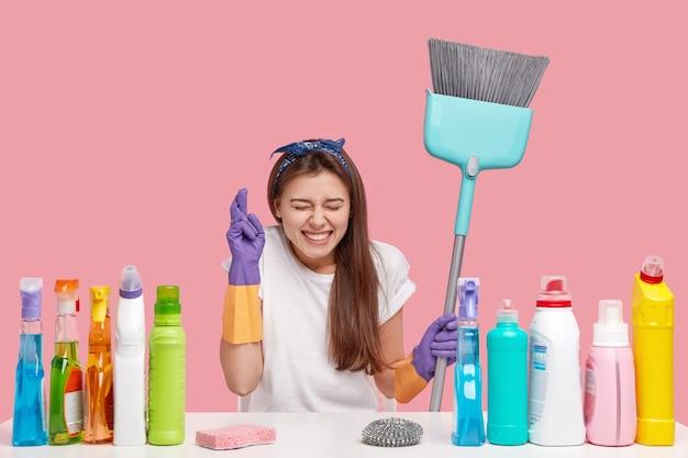 Bild der wünschenswerten hübschen jungen frau drückt die daumen für viel glück, will geldbelohnung vom kunden erhalten, arbeitet in der reinigungsdienstfirma