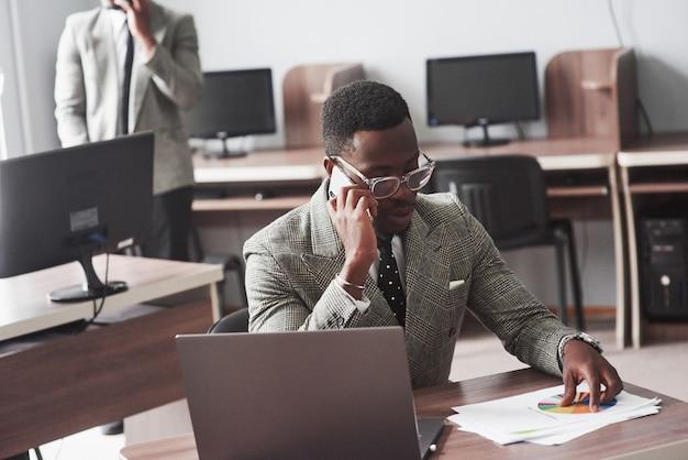 Bild des afroamerikanergeschäftsmannes arbeitend an seinem laptop