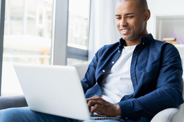 Bild des afroamerikanischen geschäftsmannes, der an seinem laptop arbeitet. hübscher junger mann an seinem schreibtisch.
