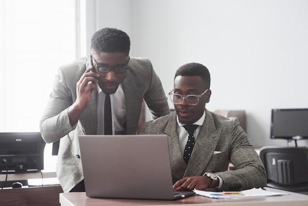 Bild des afroamerikanischen geschäftsmannes, der an seinem laptop arbeitet