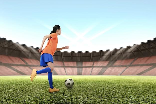 Bild des asiatischen weiblichen fußballspielers, der die kugel tritt