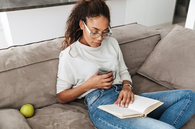Bild des attraktiven afroamerikanermädchens, das buch liest und tee trinkt, während auf sofa in der hellen wohnung sitzt
