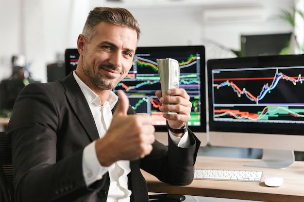 Bild des attraktiven geschäftsmanns der 30er jahre, der anzug hält packung des geldes während der arbeit im büro mit grafiken und diagrammen auf computer hält