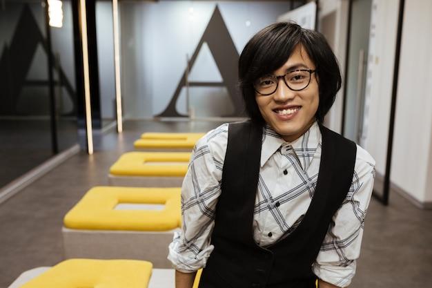 Bild des attraktiven jungen asiatischen mannes, der brille trägt, gekleidet in jacke und hemd, die drinnen stehen und beiseite schauen. coworking-konzept.
