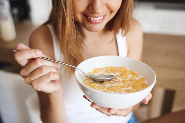 Bild des attraktiven jungen mädchens, das cornflakes mit milch an der küche isst