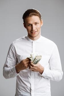 Bild des attraktiven kaukasischen mannes mit geld in den händen