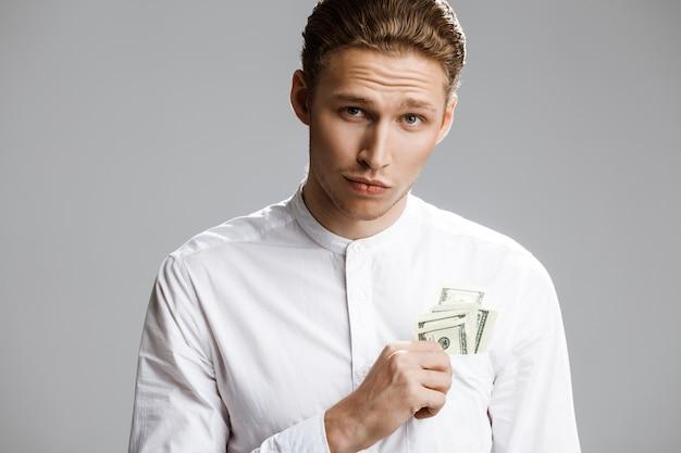 Bild des attraktiven kaukasischen mannes mit geld in einer tasche