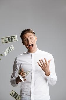 Bild des attraktiven kaukasischen mannes mit geld