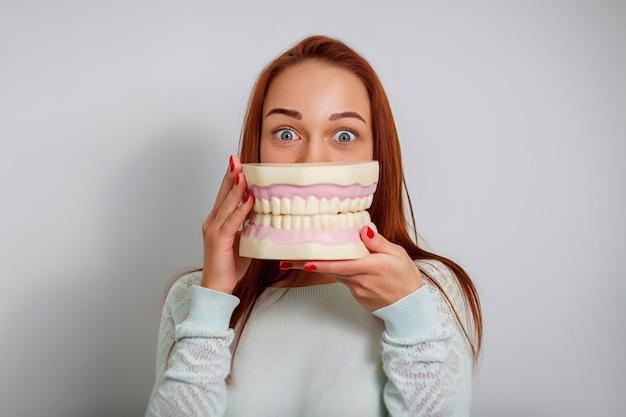 Bild des attraktiven weiblichen zahnarztpatienten mit den großen kiefern.