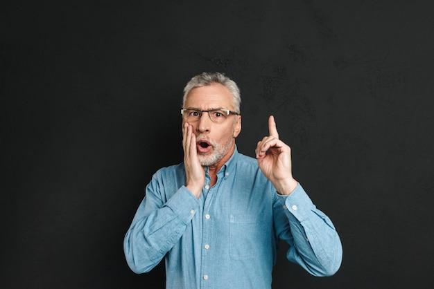 Bild des aufgeregten pensionierten mannes 60s mit grauem haar und bart im hemd, das in überraschung schreit, haben idee und zeigt zeigefinger auf copyspace nach oben, isoliert über schwarzer wand