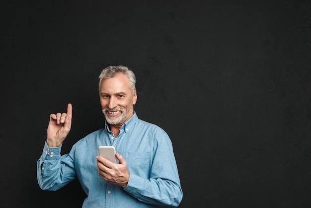 Bild des bärtigen männlichen rentners 60s mit grauem haar, das finger nach oben zeigt, wie idee haben, während handy, lokalisiert über schwarzer wand