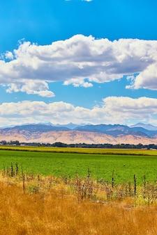Bild des bauernhoffeldes mit großen wüstenbergen in der ferne und weißen wolken