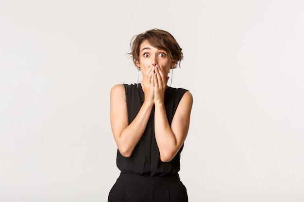 Bild des beeindruckten sprachlosen mädchens, das nach luft schnappt, mund mit den händen bedeckt und überrascht in die kamera starrt.