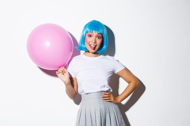 Bild des dummen partygirls in der blauen perücke, die feiertag feiert, rosa ballon hält und zunge zeigt, stehend zurückgreift.