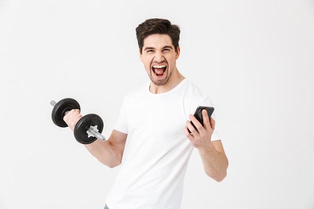 Bild des emotionalen glücklichen aufgeregten jungen mannes, der lokalisiert über der weißen wand posiert, die hantel hält, machen übung mit dem handy.