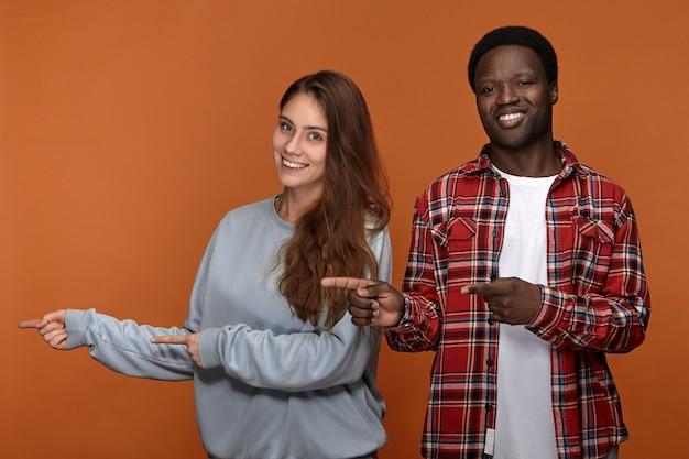 Bild des emotionalen überglücklichen jungen afroamerikanischen kerls im karierten hemd, das mit seiner entzückenden freundlich aussehenden kaukasischen freundin aufwirft, vorderfinger zur seite zeigt und breit lächelt
