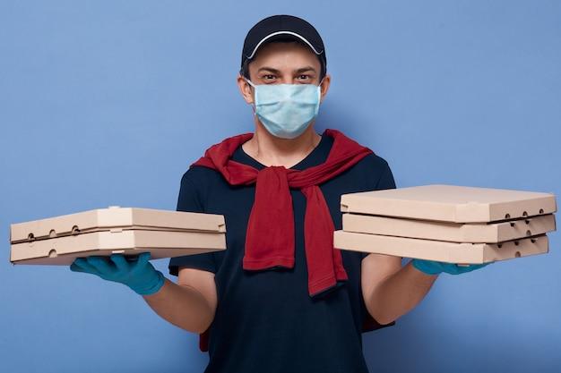 Bild des energetischen angenehmen lieferboten, der kartonschachteln mit essen hält, schutzmaske und handschuhe trägt, sich an regeln hält und direkt in die kamera schaut