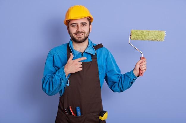 Bild des energetischen charismatischen gut aussehenden jungen arbeiters, der aufrichtig lächelt, bei der arbeit ist, geste macht, rolle in einer hand hält, richtung mit zeigefinger zeigt. berufskonzept.