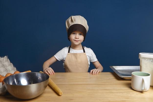 Bild des entschlossenen aufgeregten kleinen jungen, der kochuniform trägt, die am küchentisch mit metallschale steht
